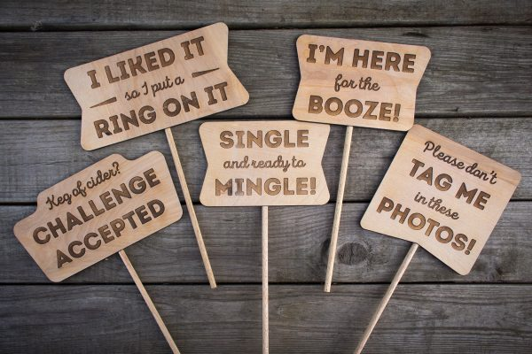 Overhead shot of five different wooden laser etched photo booth props with various fun sayings etched into the wood.