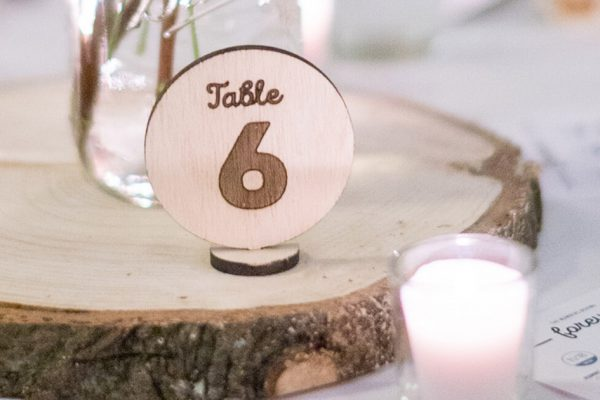 Close up view of a wooden laser etched table number.