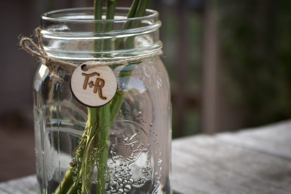 Close up view of laser etched monogram in wood hanging from a mason jar with twine.